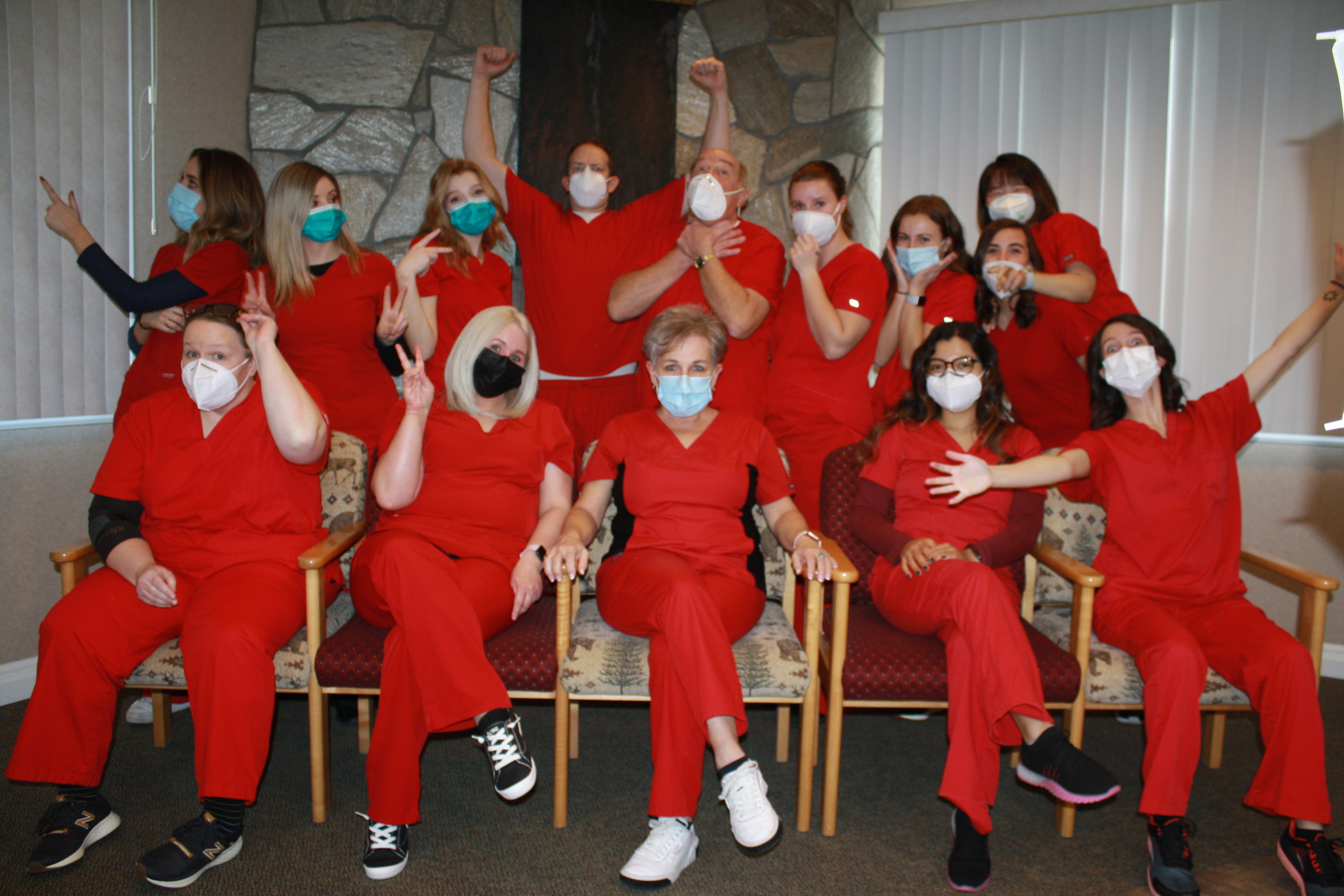 Mirci Dental Team all wearing red scrubs and looking fun